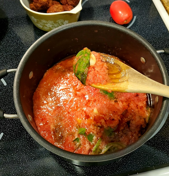 this is a fresh pot of crushed tomatoes being made into a bolognese sauce for lasagna