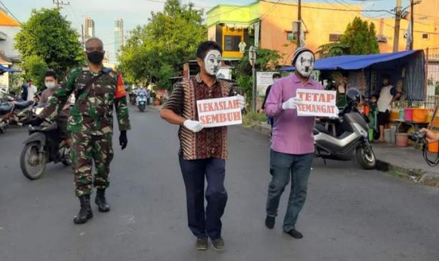 Aksi pantomim oleh relawan satgas covid