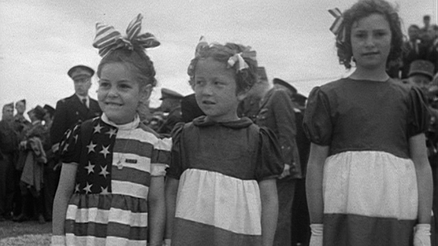 Three little girls wear dressed made from flags