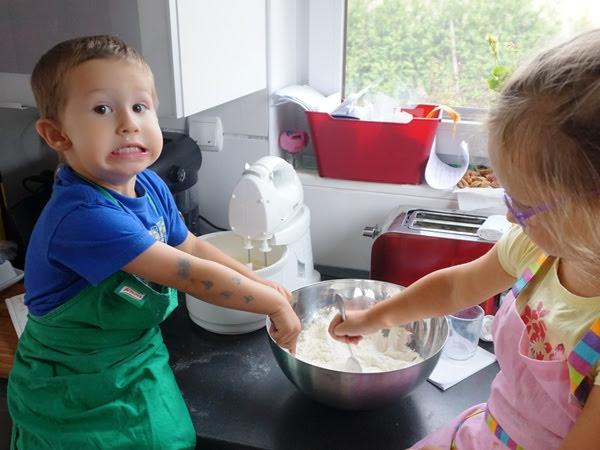 trzylatek pomaga w pieczeniu tortu