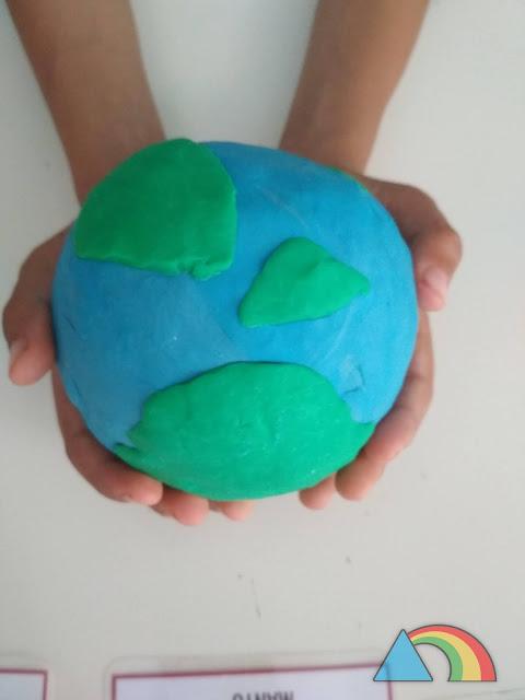 Planeta Tierra hecho con plastilina en las manos de un niño