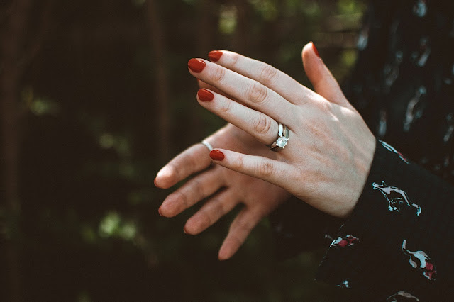 Close up of a pair hands with red nail polish and silver ring.