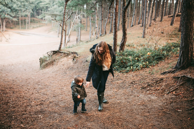 image shows a mother and toddler son walking through the woods in autumn. They are dressed in warm clothes.