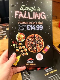A picture of a large rectangular black piece of card with dough is falling in white font with £14.99 in smaller white font with pictures of drinks and circular pizzas at the bottom on a bright background