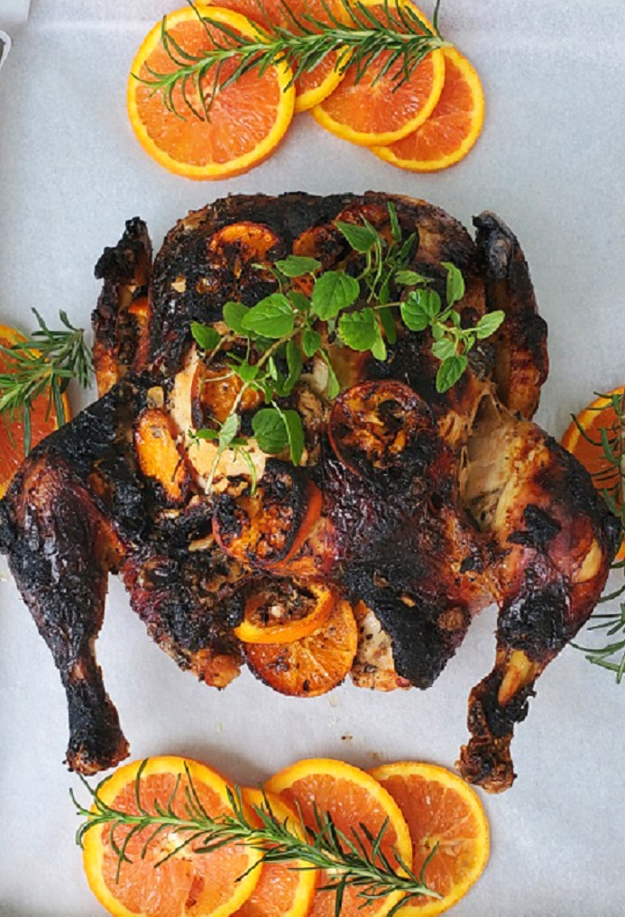 this is a whole roasting chicken basted with blood oranges and honey along with fresh herbs