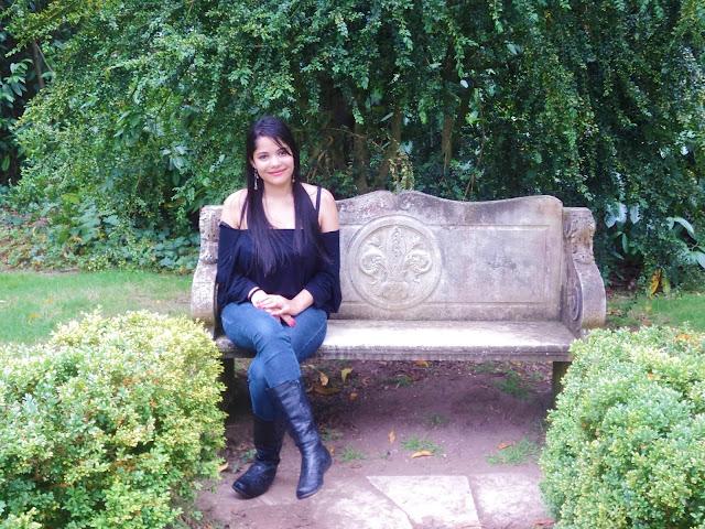menina sentada em um banco de concreto no jardim