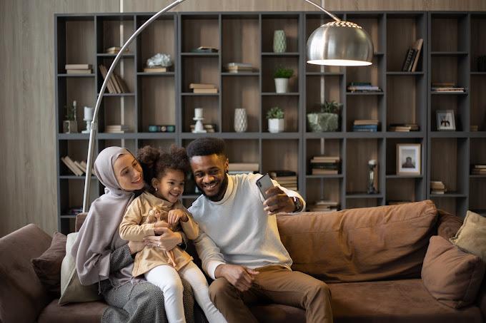 Família no sofá tirando uma selfie com o celular. Ao fundo, estante de nichos com livros e plantas.
