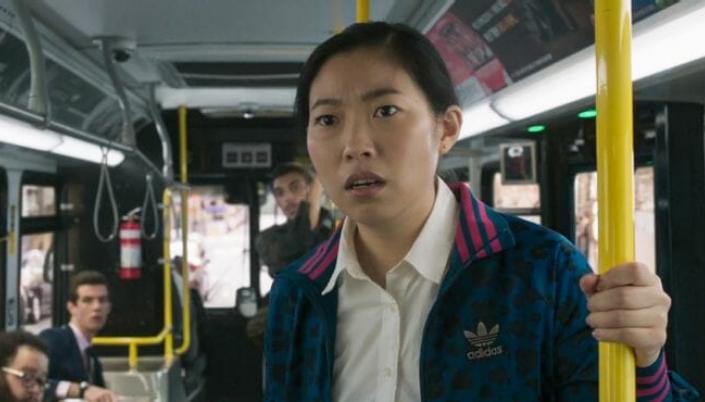 Imagem: a personagem Katy, interpretada por Awkwafina, uma mulher asiática de cabelos pretos presos em um rabo de cavalo, num casaco azul com detalhes brancos, observando algo assustada em um ônibus cheio de gente.