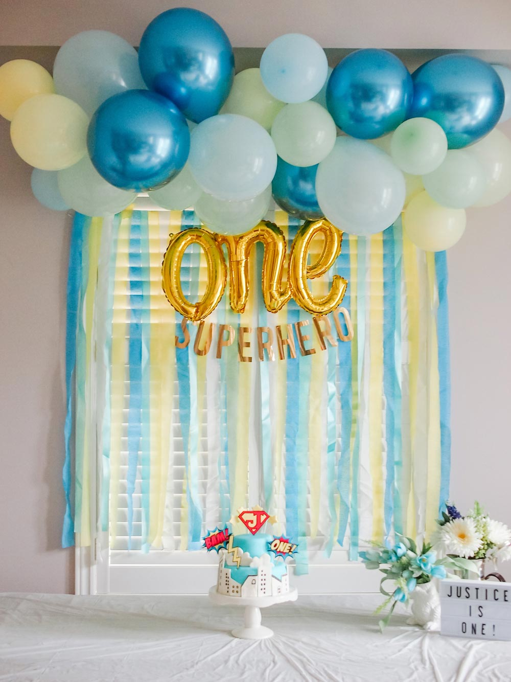 Superhero First Birthday Party - DIY Balloon Garland and streamers backdrop