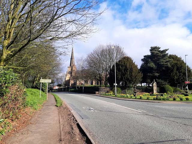 Image shows St Oswald's Church, Winwick, with the public fountain (now disused) in the foreground to the right.  The roads are empty of traffic
