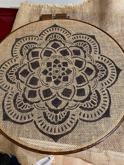Photo of mandala stenciled burlap being put into quilting hoop