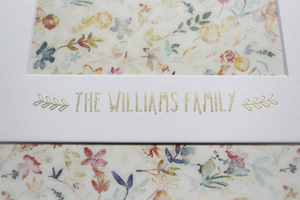 family name with gold leafy design imprinted on photo frame mat with floral paper behind it
