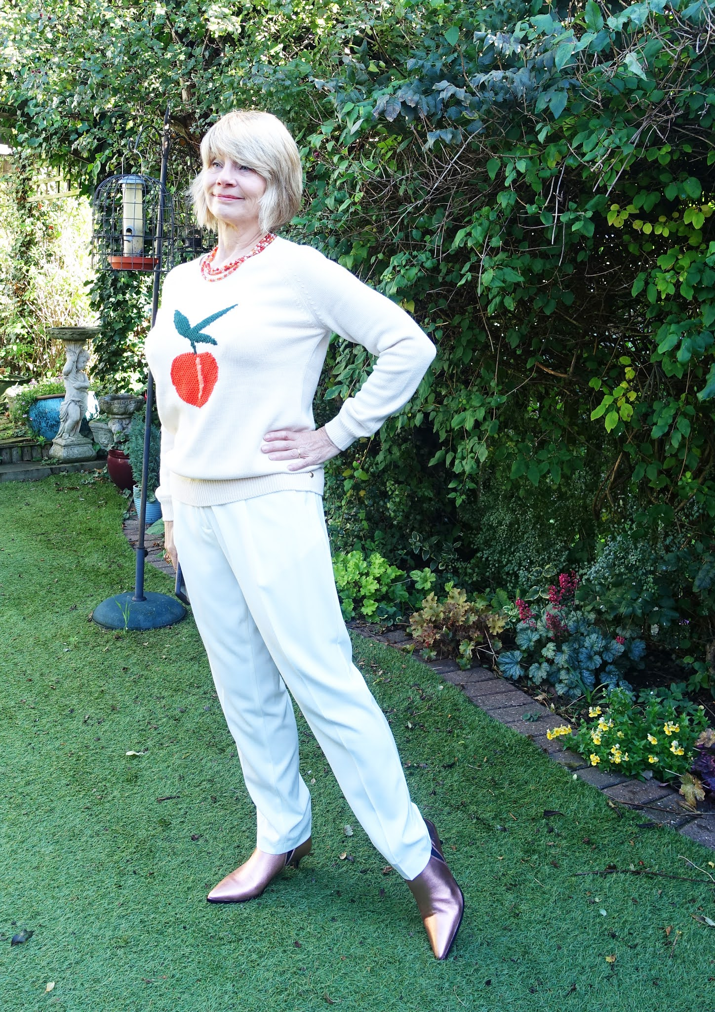 A fun but timeless look for Is This Mutton blogger Gail Hanlon in an all-cream outfit with a peach motif jumper and rose gold boots