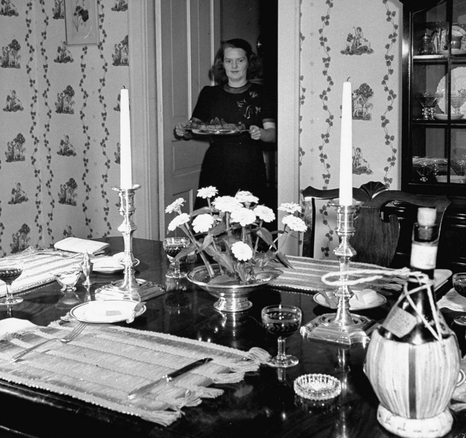 Jane prepares for dinner party by carrying a roast beef platter to the dining table she has carefully set with colorful placemats, silver candlesticks and silver centerpiece with flowers and a bottle of Chianti, as her guests finish cocktails in the living room.