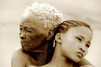A sepia-toned photo of an old gray-haired woman and a young girl. San woman and granddaughter.