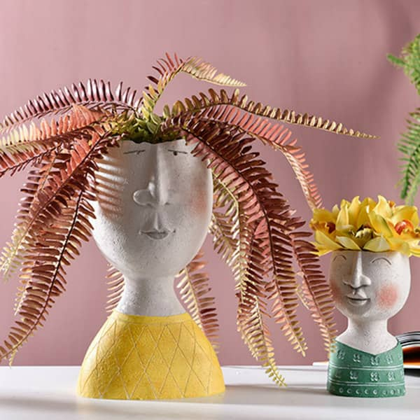 pair of head vases containing fern and flowers