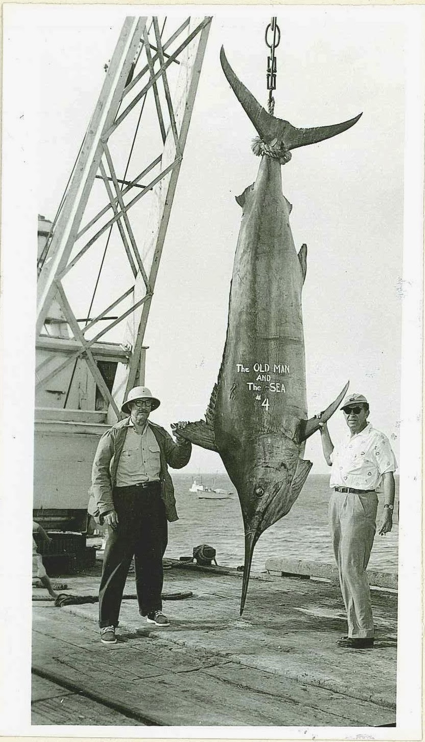 "A photograph of two men in front of a hanging marlin. The text ""The Old Man and the Sea #4"" is painted on the fish."