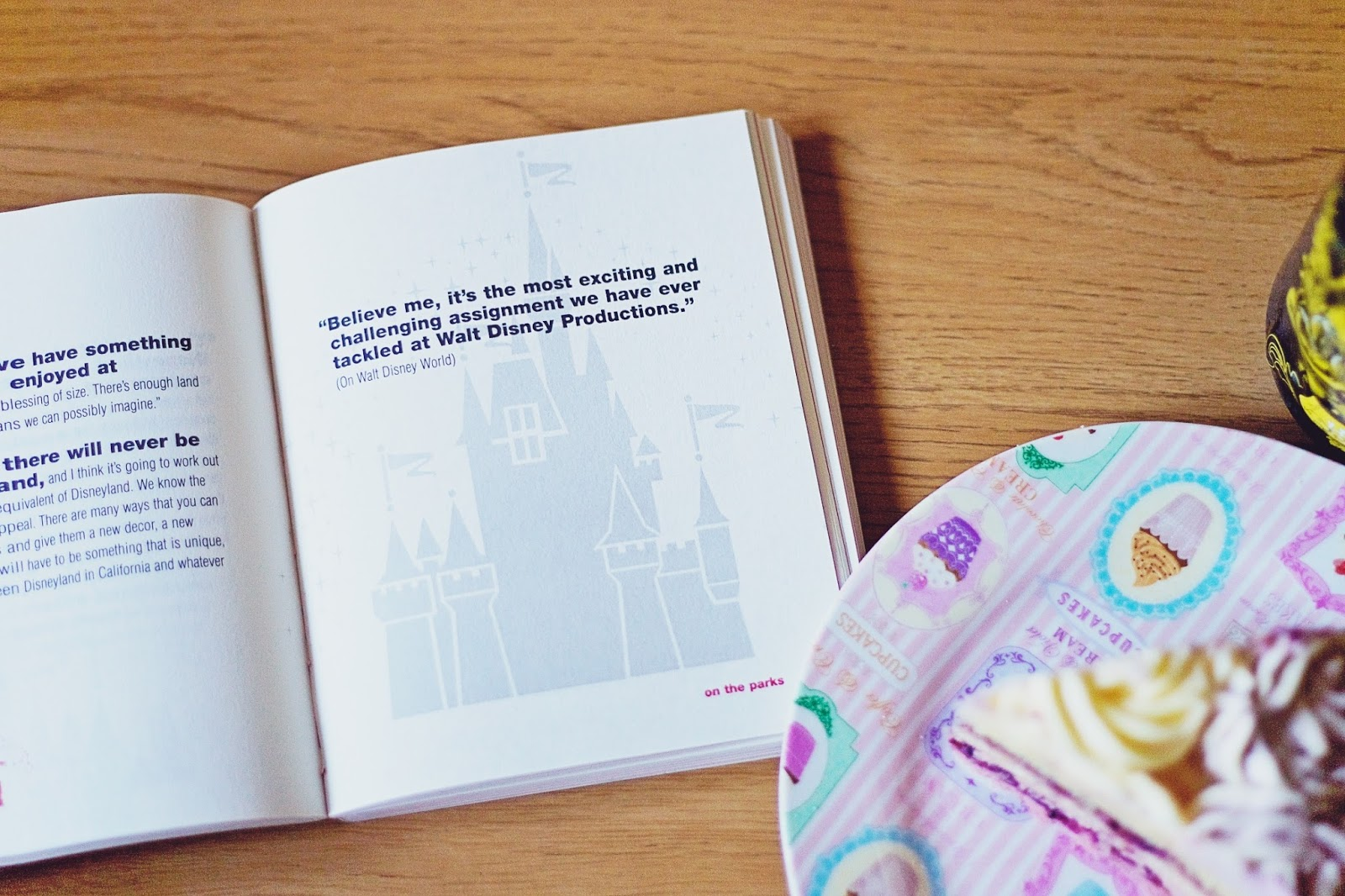 Open copy of The Quotable Walt Disney book with tea and cake.