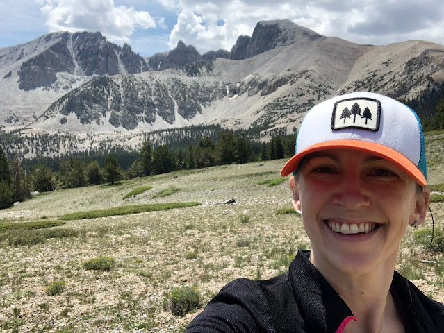 woman in a baseball hat in front of a mountain