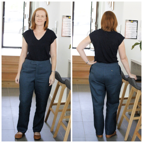a white lady posing in teal linen pants and a navy top