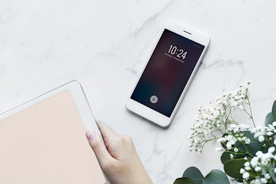 iPhone on a white table with an open book