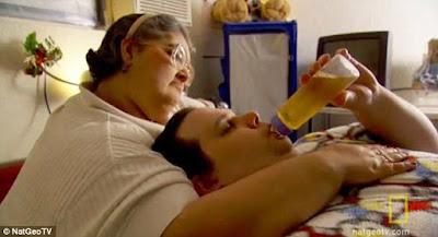 Stanley Thornton é alimentado com mamadeira pela colega de quarto Sandra Dias, uma ex-enfermeira, que morreu em julho deste ano