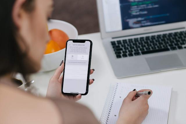 Mulher com celular na mão escrevendo em um caderno sobre a mesa em seu home office