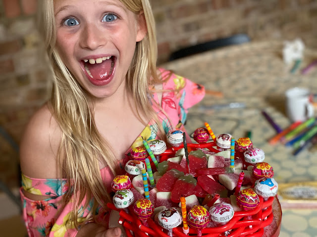 An excited birthday girl at her party holding her birthday cake which is completely made from sweets from a liquorice and lollipop outside to lots of soft jelly sweet fillings