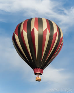 Cramer Imaging's fine art photograph of one tri-color rainbow hot air balloon taking flight in Panguitch Utah with a blue partly cloudy sky