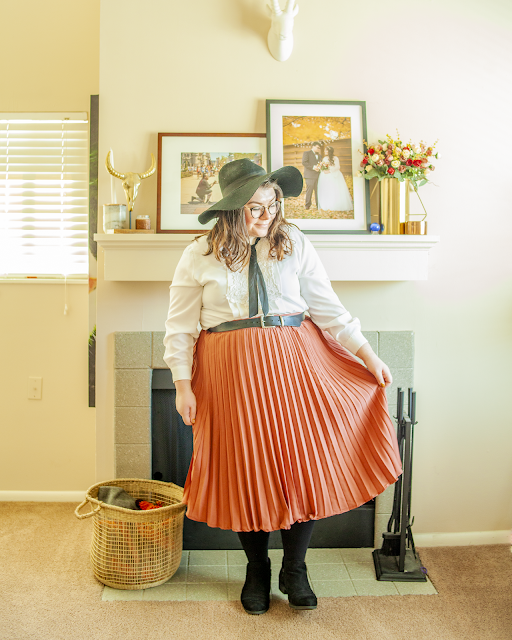 An outfit consisting of a black wide brim hat, a white ornate bodice blouse tucked into a rose colored skirt and black boots.