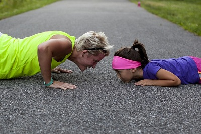 Mom and Daughter Doing Pushups on the Ground