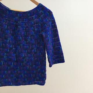 Blue crochet top hanging on a hanger