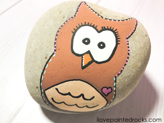 Add dots and detail to the outline of the owl painted rock for greater effect