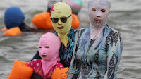 Three people in the water wearing masks that cover their whole faces and suits that completely cover their bodies.
