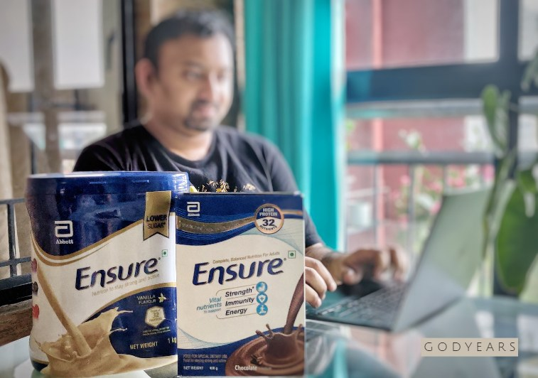 Man working on laptop beside protein supplement Ensure