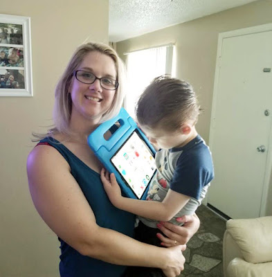 Jennifer holds David while he uses the iPad
