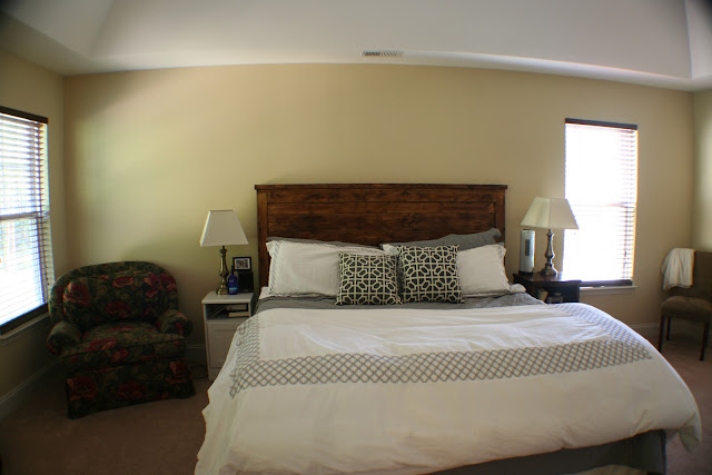A bedroom with a dark wood headboard and gray bedding with a beige wall color