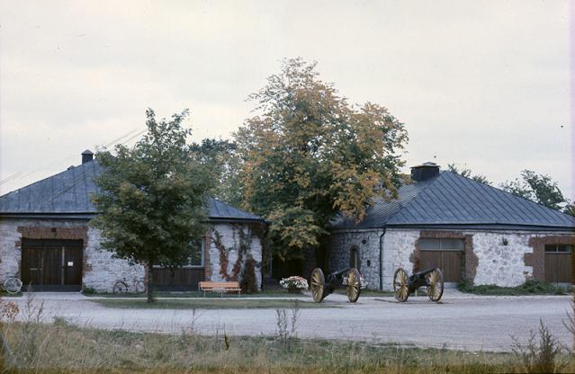 Etelä-Karjalan museo etelästä kuvattuna syksyllä. Kuvassa näkyy tykkejä. Kuva on synkkä ja harmahtava. Etelä-Karjalan museota hämärtää kaksi isompaa puuta.