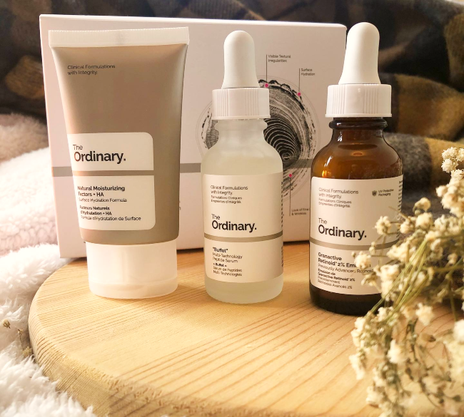 Thre bottles of The Ordinary Skincare on a brown chopping board