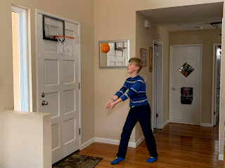 A boy in black pants and a black and blue striped shirt hits a small basketball with his arms in a house.