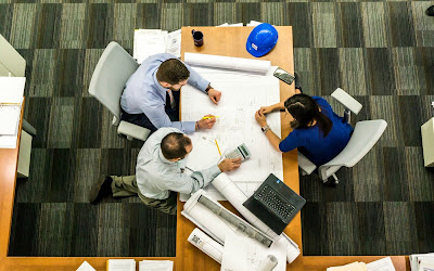 Gestores discutiendo en torno a una mesa, con calculadora y planos