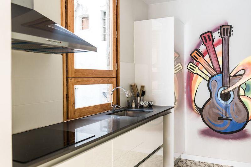 Apartamento con muebles de cartón y la instalación vista. Cocina pequeña con ventana original forrada con doble cristal y vinilo en la pared