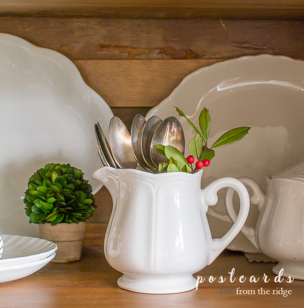 small white ironstone creamer with vintage silver and holly clippings