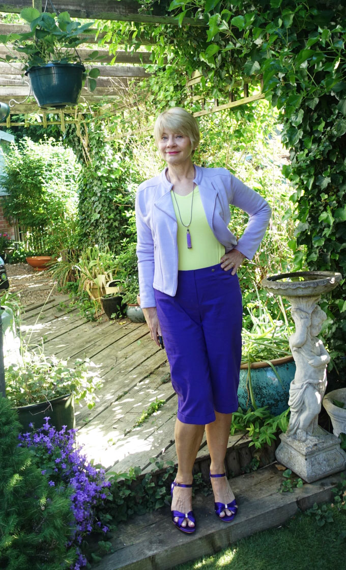 Gail Hanlon in smart casual wear: purple knee length shorts, lavender Chloe jacket by Kettlewell and acid yellow top