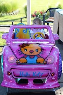 pinkes Auto, in das sich Kinder setzen können, um gegen Münzeinwurf rumschaukeln zu können
