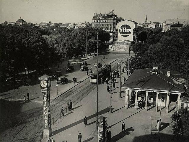 1933 год. Rīga. Brīvības bulvāris. Часы еще с рекламой шоколадной фабрики «Th. Riegert» и строящейся монумент Свободы