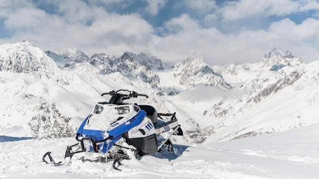an icy snowmobile after its trek to the top of a mountain