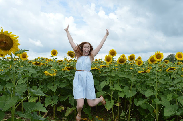 beautiful red head girl jumping in a field of sunflowers