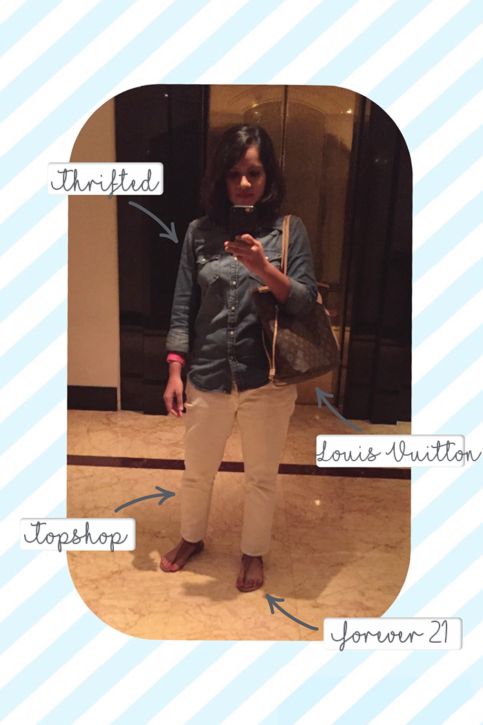 An image of a young woman wearing a blue denim shirt with white jeans, tan sandals and a louis vuitton monogram handbag taking a selfie in a mirror at a hotel