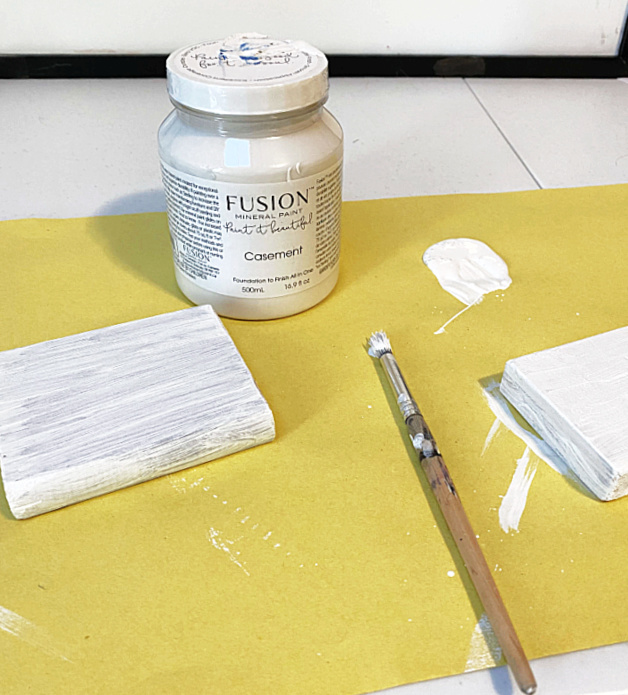 Painted wood scraps and jar of white paint